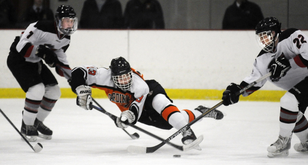 Gardiner Area High School's Tristan Hebert, center, stick handles between Maranacook-Winthrop's Bailey Clark, left, and Bailey Stockford during a Western B hockey game Wednesday afternoon at Kents Hill.
