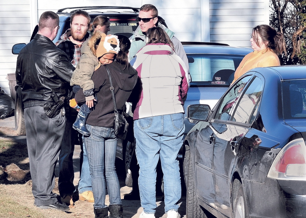 Maine State Police Detective Christopher Tupper, left, and Waterville Detective Lincoln Ryder, at right, question Justin DiPietro after he arrived at his home on Violette Ave. in Waterville on Sunday, Dec. 18, 2011, as an extensive search was underway at his home and the neighborhood for his 20-month-old daughter Ayla Reynolds.