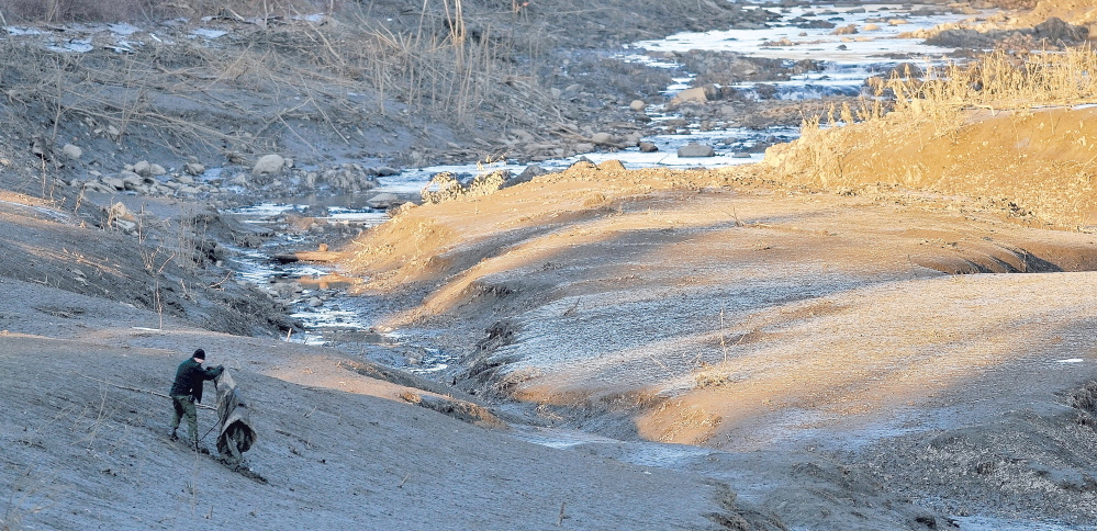 A searcher scours the emptied river bed of the Messalonskee Stream along West River Road near the intersection of Kennedy Memorial Drive in Waterville Dec. 20, 2011, afternoon for a missing 20 month old girl.