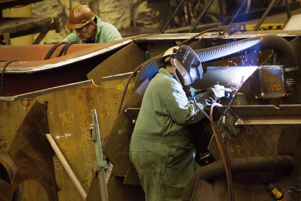 Shipbuilders work on the assembly of ship interior components at Bath Iron Works in Bath on Wednesday