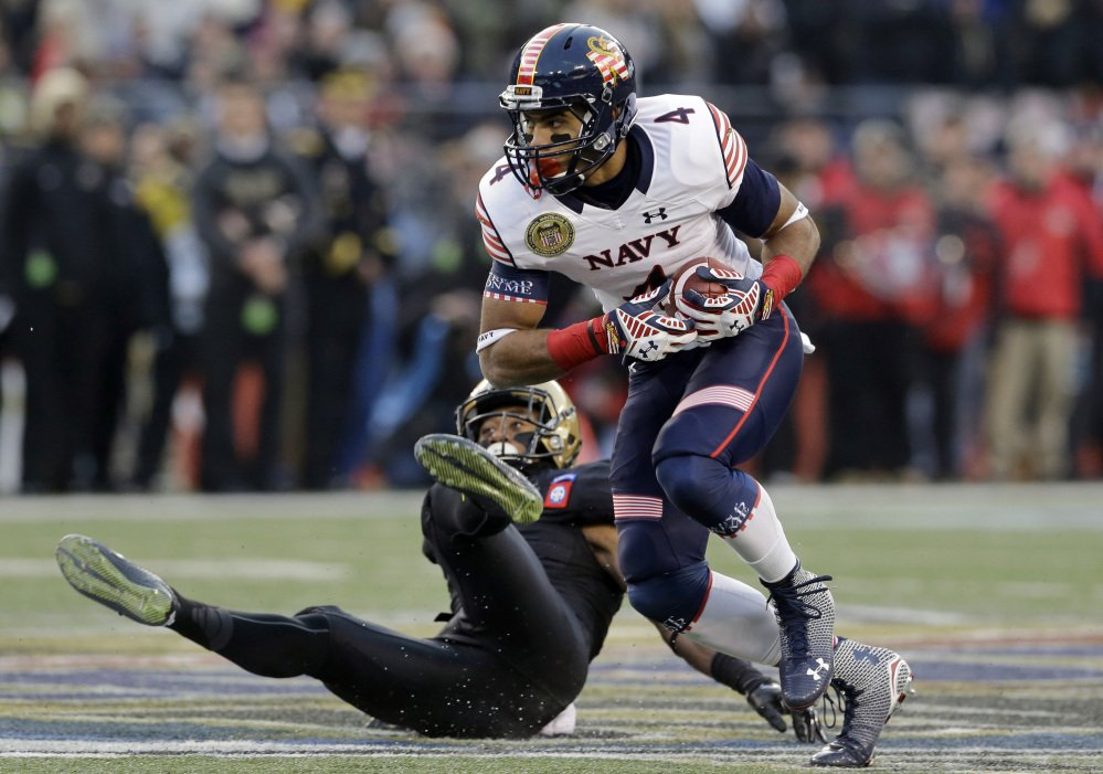 Navy wide receiver Jamir Tillman, 4, rushes past Army defensive back Josh Jenkins for a first down in the first half of the Army-Navy game Saturday in Baltimore. Navy won 17-10, its 13th victory in a row over Army.