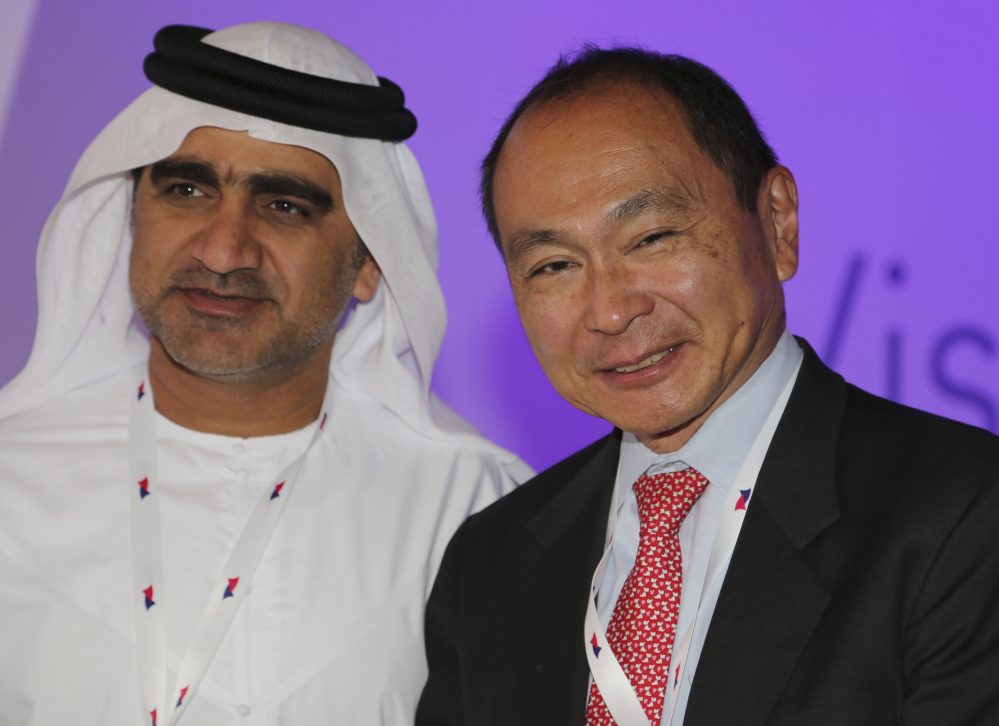 Francis Fukuyama, an American political scientist, political economist and author, right, poses for a photo with an Emirati official at the Arab Strategy Forum in Dubai, United Arab Emirates, on Sunday. Abdullah al-Badri, the secretary-general of OPEC, is urging Gulf Arab nations to continue investing in oilfield development despite the sharp slide in crude prices.