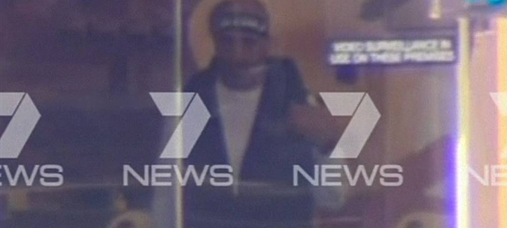 These images taken from video show, above, a man believed to be a gunman inside a Sydney cafe and, top, people inside the cafe holding what appears to be a black flag with white Arabic writing on it.