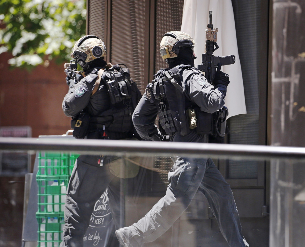 A police officer runs across Martin Place near the Lindt Chocolat Cafe, where hostages were being held by a gunman Monday morning in central Sydney. It was not known how many hostages were in the cafe, or what motivated the incident.