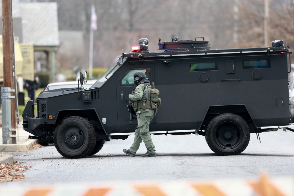 Police move near the scene of a shooting Monday, , in Souderton, Pa. Police are surrounding a home in Souderton, outside Philadelphia, where a suspect is believed to have barricaded himself after shootings at multiple homes.