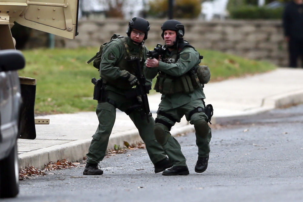 Police move near the scene of a shooting Monday, in Souderton, Pa. Police are surrounding a home in Souderton, outside Philadelphia, where a suspect is believed to have barricaded himself after shootings at multiple homes.