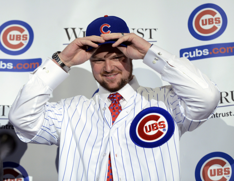 Pitcher Jon Lester puts on a Chicago Cubs jersey and hat after being introduced as a member of the Chicago Cubs baseball team during a news conference in Chicago on Monday. Lester agreed to a $155 million, six-year contract with the Cubs at the winter meetings last week that set baseball records for largest signing bonus and biggest upfront payment.