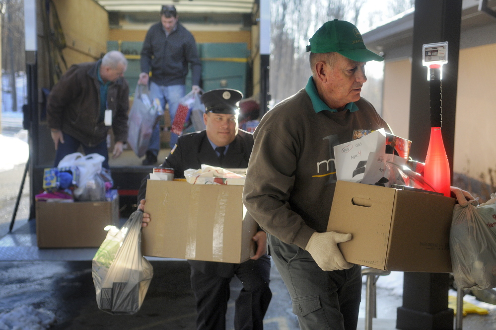 Togus employees, from right, Stan Coutts, Quinten Toothaker, Greg Veilleux and Harold Elliott unload gifts from the federal hospital's employees at the Salvation Army in Augusta on Monday.