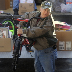 Togus employee Mahlon Lincoln unloads a bike donated by the federal hospital's employees at the Salvation Army in Augusta on Monday. The ride will be given to a child in the area during the holidays.