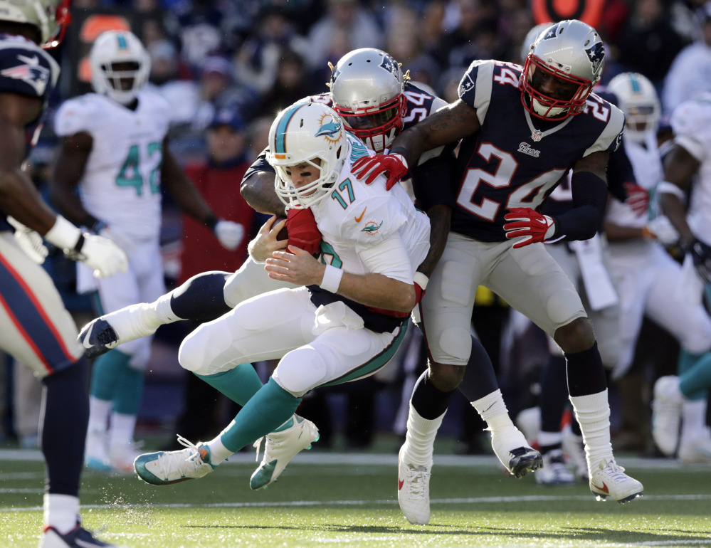 New England Patriots outside linebacker Dont'a Hightower, rear, tackles Miami Dolphins quarterback Ryan Tannehill (17) alongside Patriots cornerback Darrelle Revis (24) in the first half Sunday in Foxborough, Mass. The Patriots won 41-13 to clinch the AFC East title.