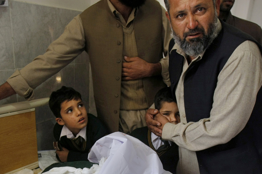 A Pakistani man comforts a student standing at the bedside of a boy who was injured in a Taliban attack on a school, at a local hospital in Peshawar, Pakistan, Tuesday, Dec. 16, 2014. Taliban gunmen stormed a military-run school in the northwestern Pakistani city of Peshawar on Tuesday, killing more than 100, officials said, in the worst attack to hit the country in over a year.(AP Photo/Mohammad Sajjad)