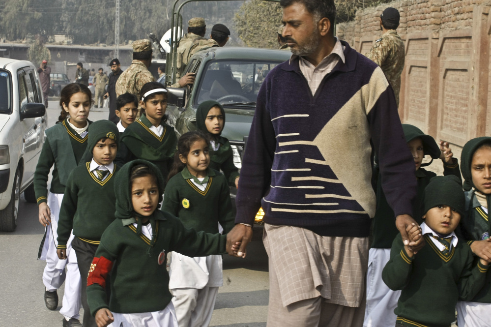 A plainclothes security officer escorts students evacuated from a school as Taliban fighters attack another school nearby in Peshawar, Pakistan, Tuesday.