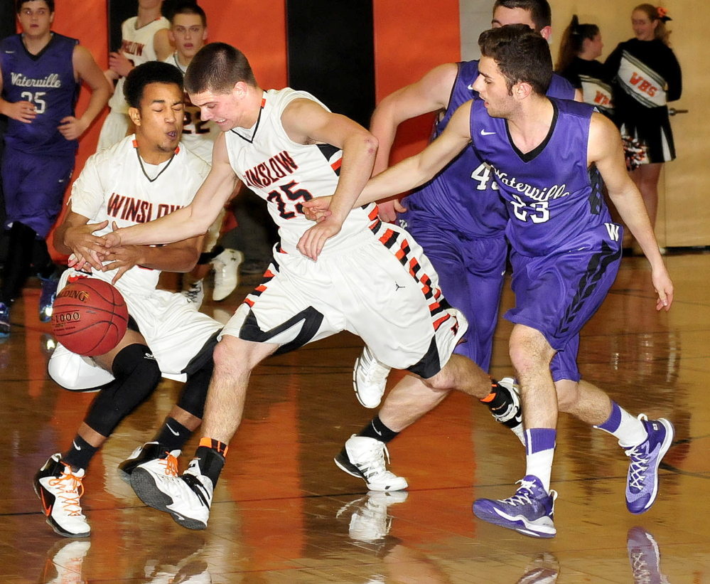 Staff photo by David Leaming   Winslow's Earle Keanu, left, and Trenton Bouchard chase a loose ball as Waterville's Nicholas Elias, left, pressures during a KVAC B game Tuesday.