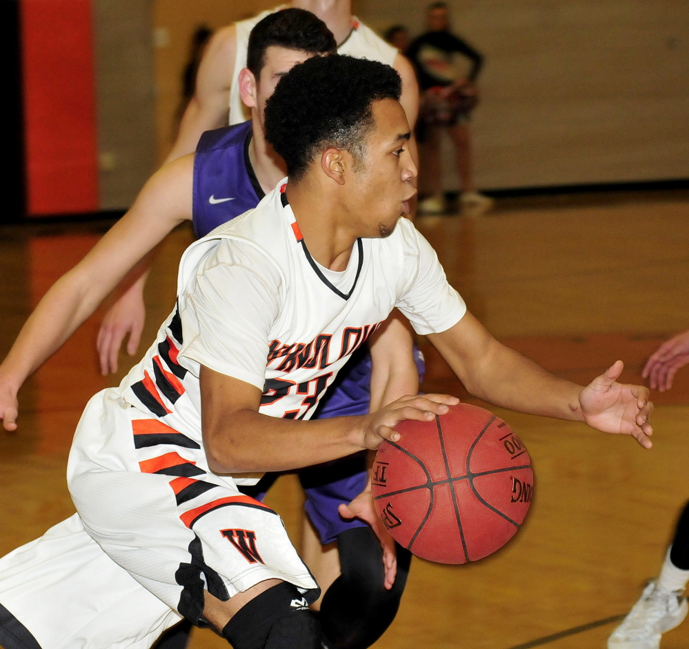 Staff photo by David Leaming   Winslow's Earle Keanu drives toward the basket during a game against Waterville on Tuesday.