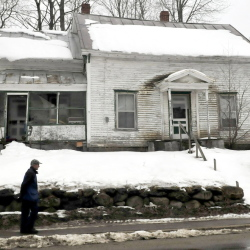 A pedestrian walks past an empty home near downtown Wilton on Tuesday. Portions of the town may benefit from federal grant money for upgrades if a percentage of the property is designated as slum and blight.