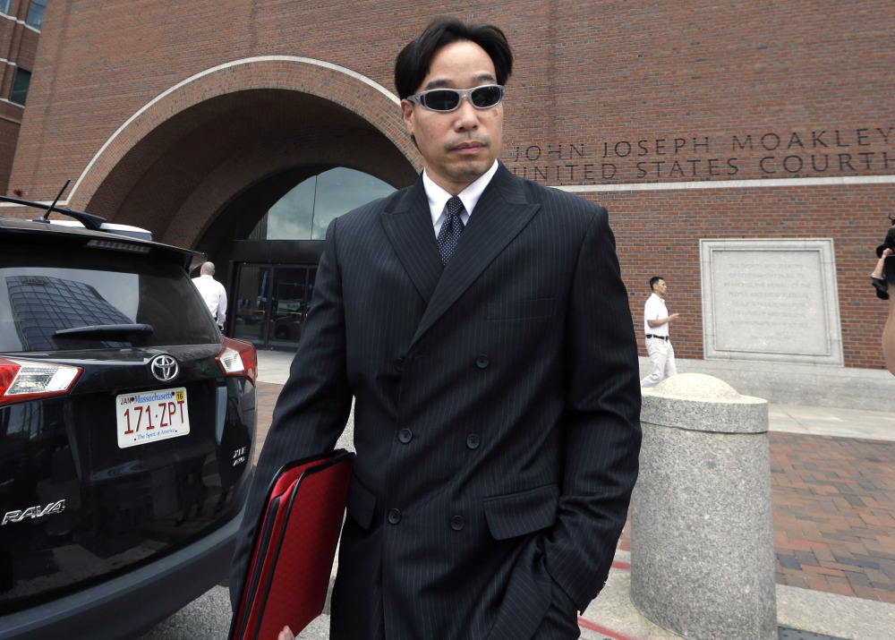 In this Sept. 11, 2014 file photo, Glenn Adam Chin, former supervisory pharmacist at the New England Compounding Center, departs federal court in Boston. Chin was among 14 people from the pharmaceutical  company arrested at their homes Wednesday, Dec. 17, 2014. Tainted steroids manufactured by the pharmacy were blamed  for a fungal meningitis outbreak that killed 64 people across the country.