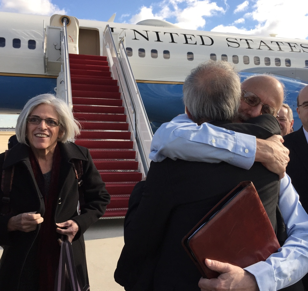 In this handout photo provided by Jill Zuckman, Alan Gross, facing camera, is hugged by Tim Rieser, an aide to Sen. Patrick Leahy, D-Vt., Wednesday, Dec. 17, 2014, at Andrews Air Force Base, Md., upon his arrival from Cuba. Gross's wife Judy is at left, Rep. Jim McGovern, D-Mass. is at right. (AP Photo/Jill Zuckman)