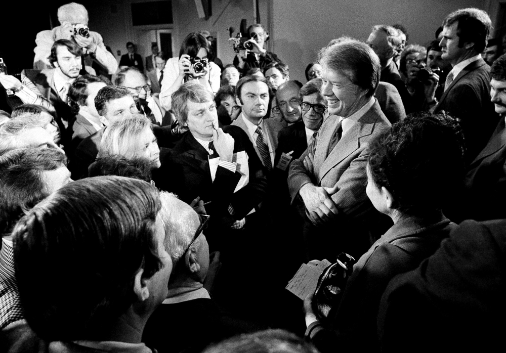 FILE - In this March 9, 1977 file photo, President Jimmy Carter, right, is surrounded by journalists after a news conference where he announced the lifting of the travel ban on Cuba, Vietnam, North Korea and Cambodia, in the executive office building in Washington, D.C. Carter tried to normalize relations with Cuba shortly after taking office in 1977, re-establishing diplomatic missions and negotiating release of thousands of prisoners. But conflicts over Cuba's military mission in Africa, tension caused by a flood of Cuban refugees in 1980 and the election of Ronald Reagan end the rapprochement. On Wednesday, Dec. 17, 2014, the U.S. and Cuba agreed to re-establish diplomatic relations and open economic and travel ties, marking a historic shift in U.S. policy toward the communist island after a half-century of enmity dating back to the Cold War. (AP Photo, File)