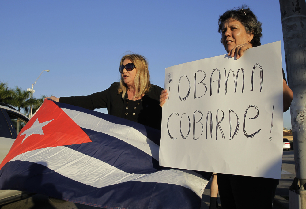 "Ana Lourdes Cuesta, left, and Liliana Cuerra, of Miami, protest in Miami, Wednesday, Dec. 17, 2014, the Obama administration's decision to re-establish diplomatic relationships with Cuba. Cuerra holds a sign that reads ""Obama coward."" (AP Photo/Marta Lavandier)"