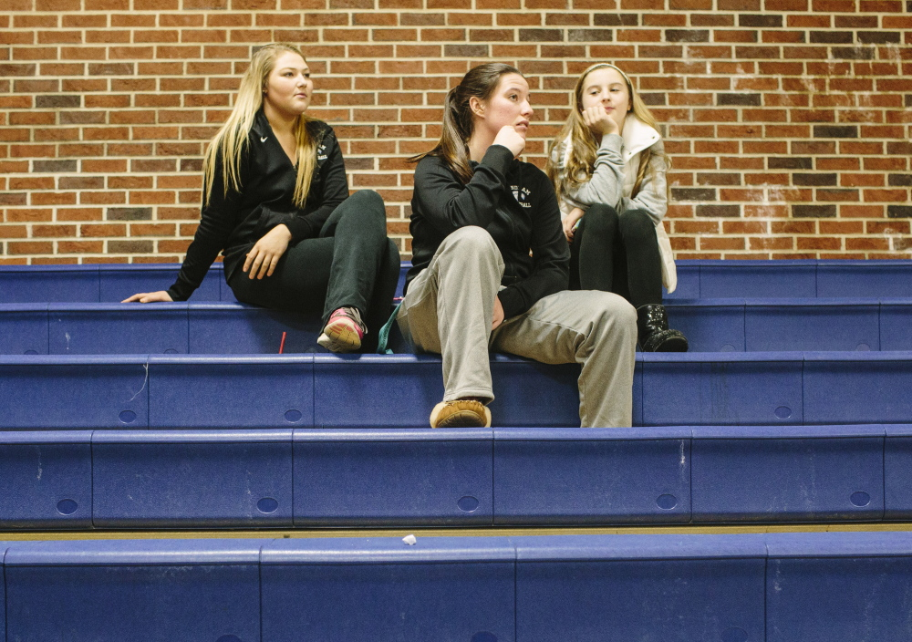 Windham varsity basketball players Julia Linevitch, left, Sadie Nelson, center, and Mya Mannette watch the boys' game Wednesday, which was moved to USM in Gorham. They said when their school was evacuated Monday they thought it was just another lockdown drill.