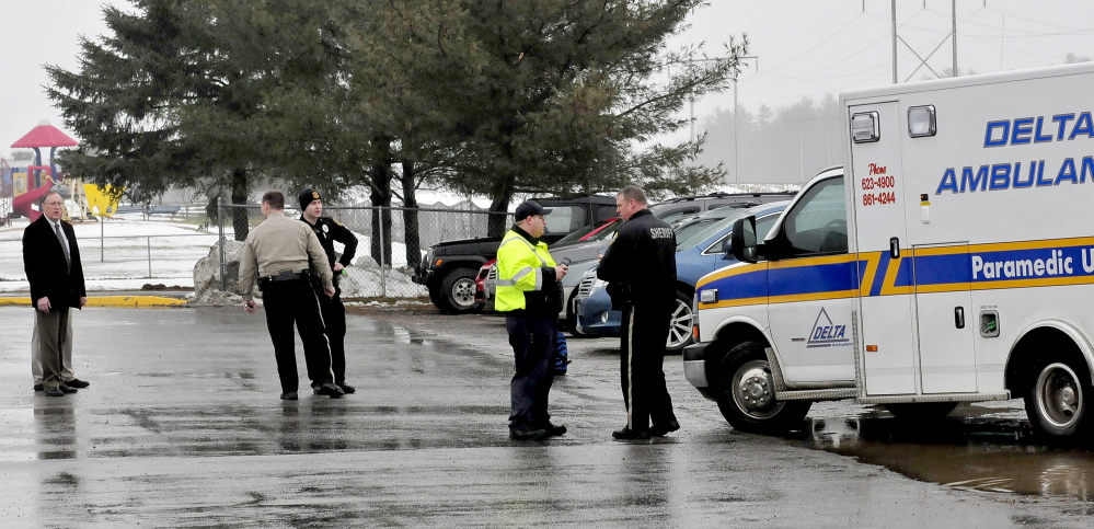 Police and school administrators including SAD 49 Superintendent Dean Baker, left, congregate in a parking lot beside an ambulance at Benton Elementary School in Benton on Wednesday afternoon. The school was placed in a lockdown after a man was seen cutting himself, a first responder said.