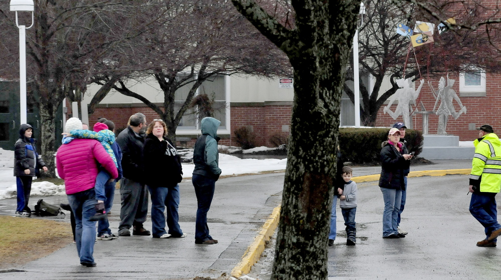 Parents of children at Benton Elementary School wait for police to allow them to pick up their children following a lockdown of the school on Wednesday, December 17, 2014.