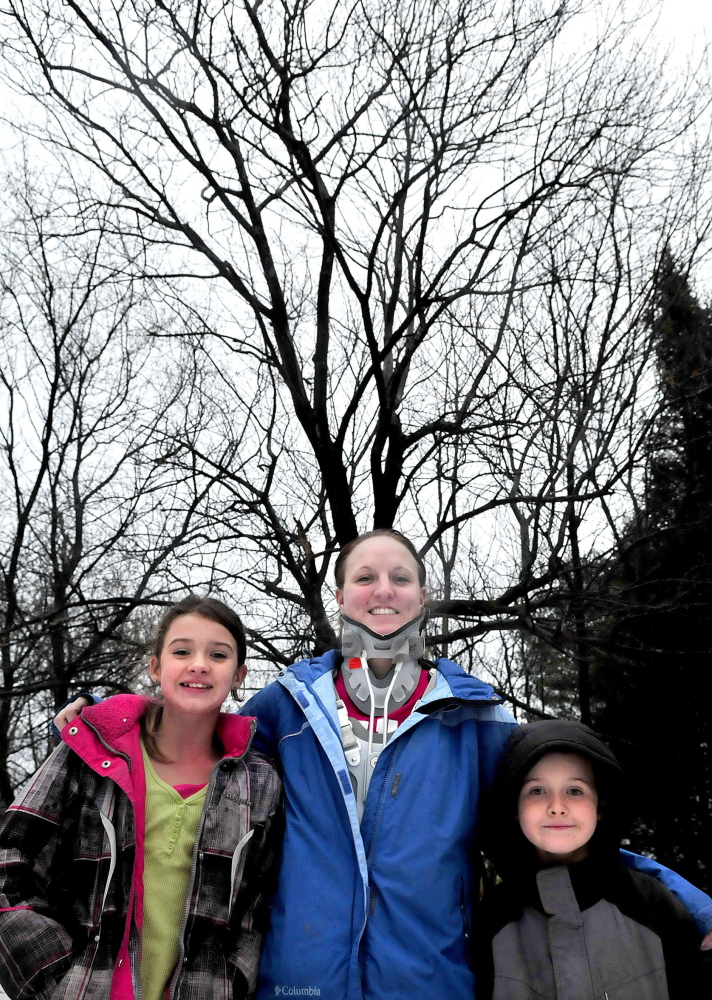 Kristin Cook and her children Alexis and Aiden stand in front of the tree that Kristin fell from in November at their home in Fairfield, breaking her neck and back. Alexis, 11, ran to a neighbor's home to summon help while Aiden, 9, stayed with his mother.