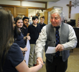 Rob Gordon, executive director of the United Way of Kennebec Valley, shakes hands Thursday with St. Michael School seventh-graders who helped raise the money at the school in Augusta for victims of two recent fires in the city.