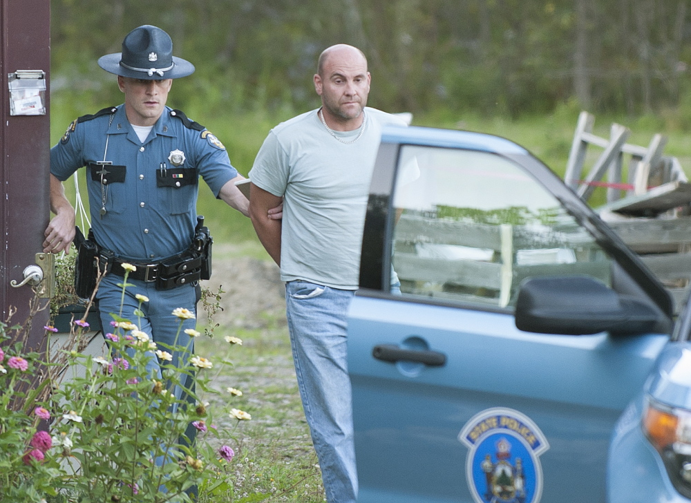 Maine State Police Trooper Scott Duff leads Marc Alberi, of Newport, to his cruiser in handcuffs Sept. 8 after serving him with a search warrant.