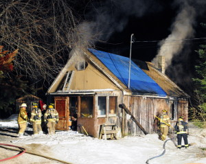 Firefighters from Winthrop and several mutual aid towns work at a house fire on Friday at 42 Maranacook Road in Winthrop.
