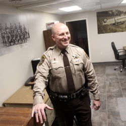 Franklin County Sheriff Scott Nichols talks about the renovations to the department in Farmington on Friday. Nichols is standing in the patrol room, which used to be divided into two rooms. The photographs on the walls are pictures of the Franklin County department from over the years.