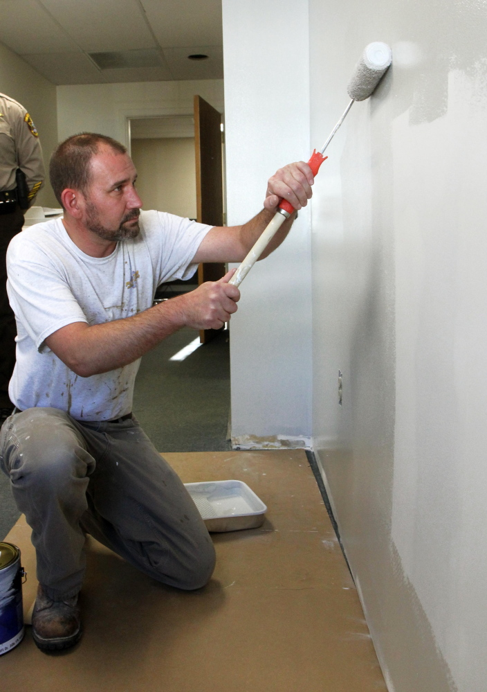 Brian Hartley of Anson finishes up painting the last room to be revovated at the Franklin County sheriff's office in Farmington on Friday.