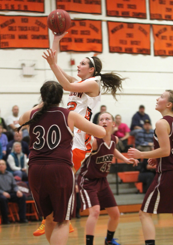 Winslow High School's Delaney Wood drives past Katie Hughes (30) and several other Maine Central Institute defenders for a basket during an Eastern B game Friday night.
