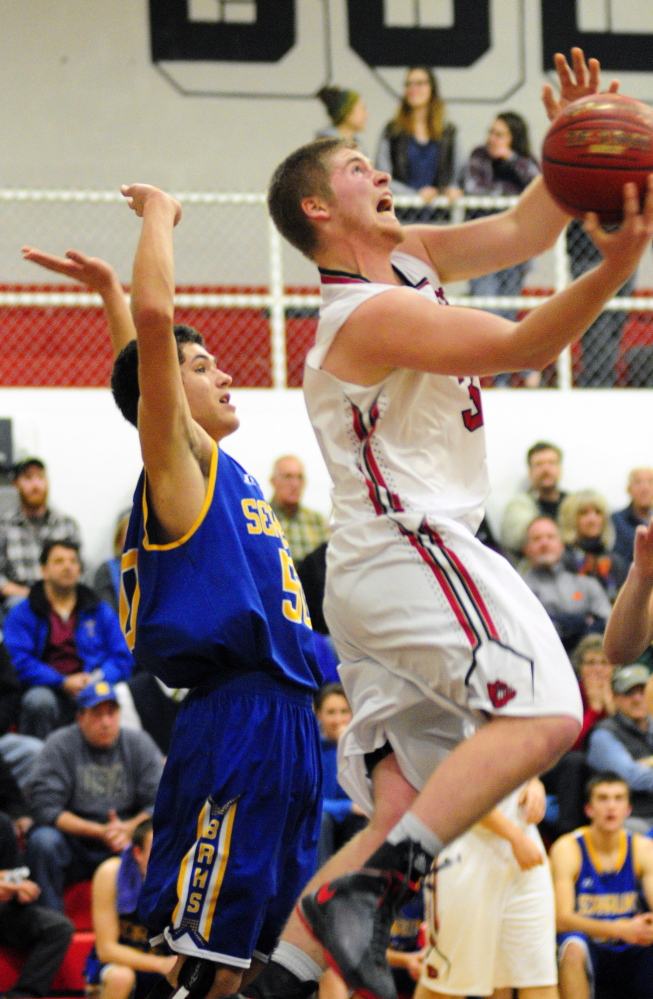 Boothbay's Abel Bryer watches as Hall-Dale's Brian Allen tries to put up a shot under the basket during a Western C game Friday in the Penny Gym at Hall-Dale High School.