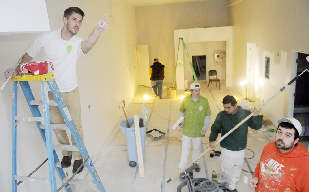 Ryan Guerrette, left, oversees a crew of painters on Thursday while painting Augusta apartments that belong to his family. Guerrette and his father, William, have opened a Wow 1 Day Painting franchise.