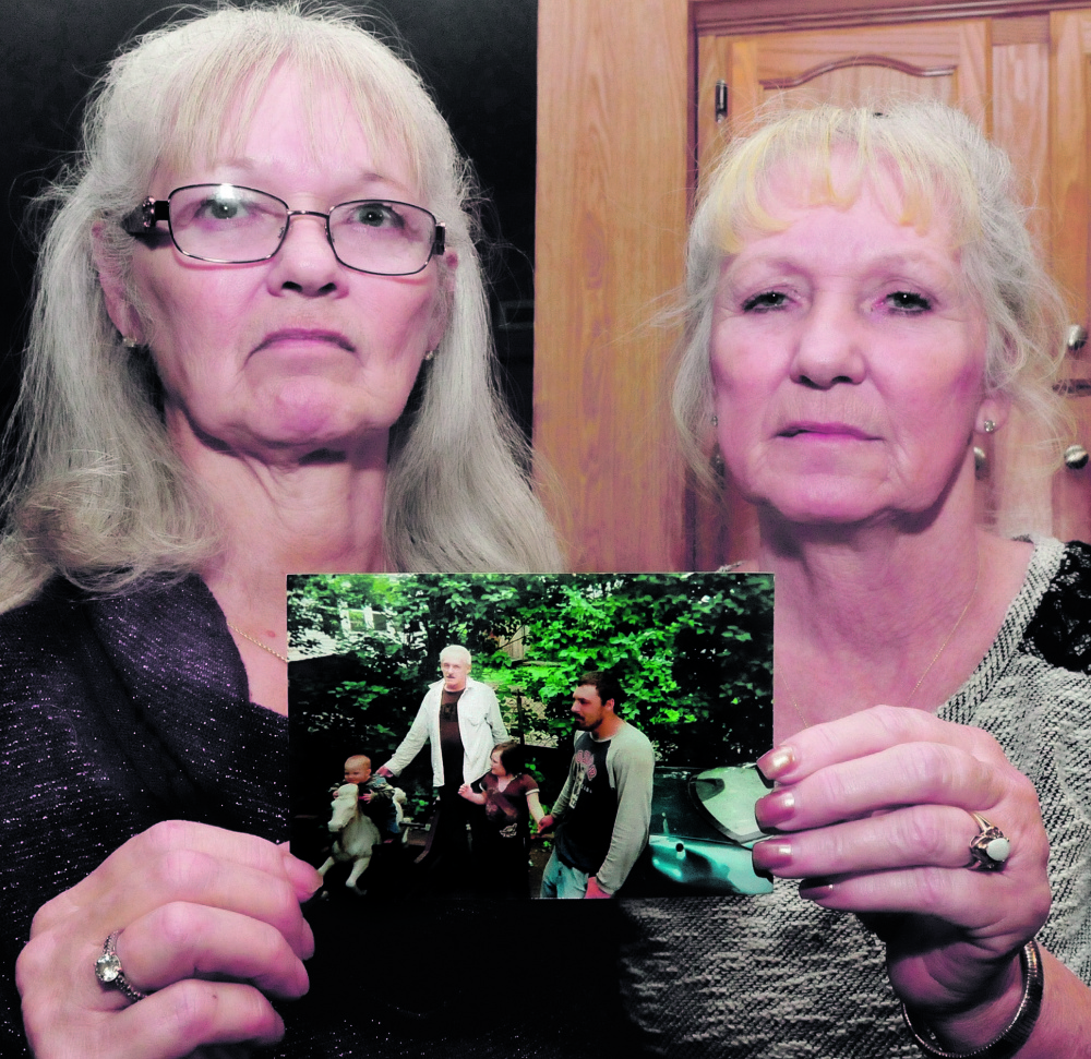 Joan Cuares, left, and Debbie Deyoung hold a photograph that shows their brother Dana Kitchin on Thursday. Kitchin was found dead Dec. 12 while incarcerated at the Kennebec County Correctional Facility in Augusta.