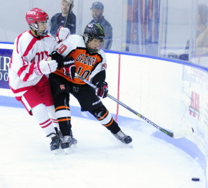 Cony's Avery Pomerleau, left, and Gardiner's Connor Manter go after the puck against the boards during a game Saturday at the Bank of Maine Ice Vault in Hallowell. Gardiner won 2-1.