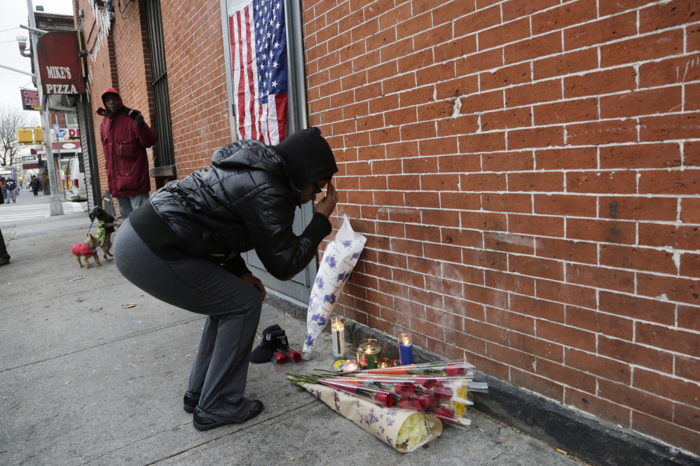 "Maria Alomar genuflects Sunday at a makeshift memorial for the two police officers who were shot there Saturday, in the Bedford-Stuyvesant neighborhood of Brooklyn. Alomar's niece is an NYPD crime scene investigator. ""It could have been her in the car,"" she said."