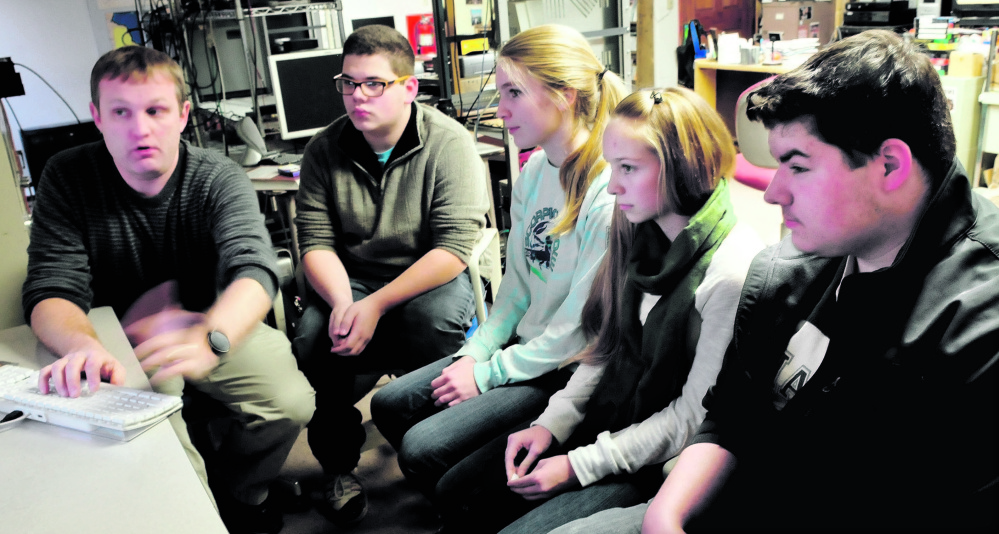 Nokomis Regional High School teacher Kern Kelley, left, logs on to a Google Hangout chat site Dec. 15 for students from left Zack Mitchell, Austin Taylor, Britney Bubar and Jake McEwen at the school in Newport.