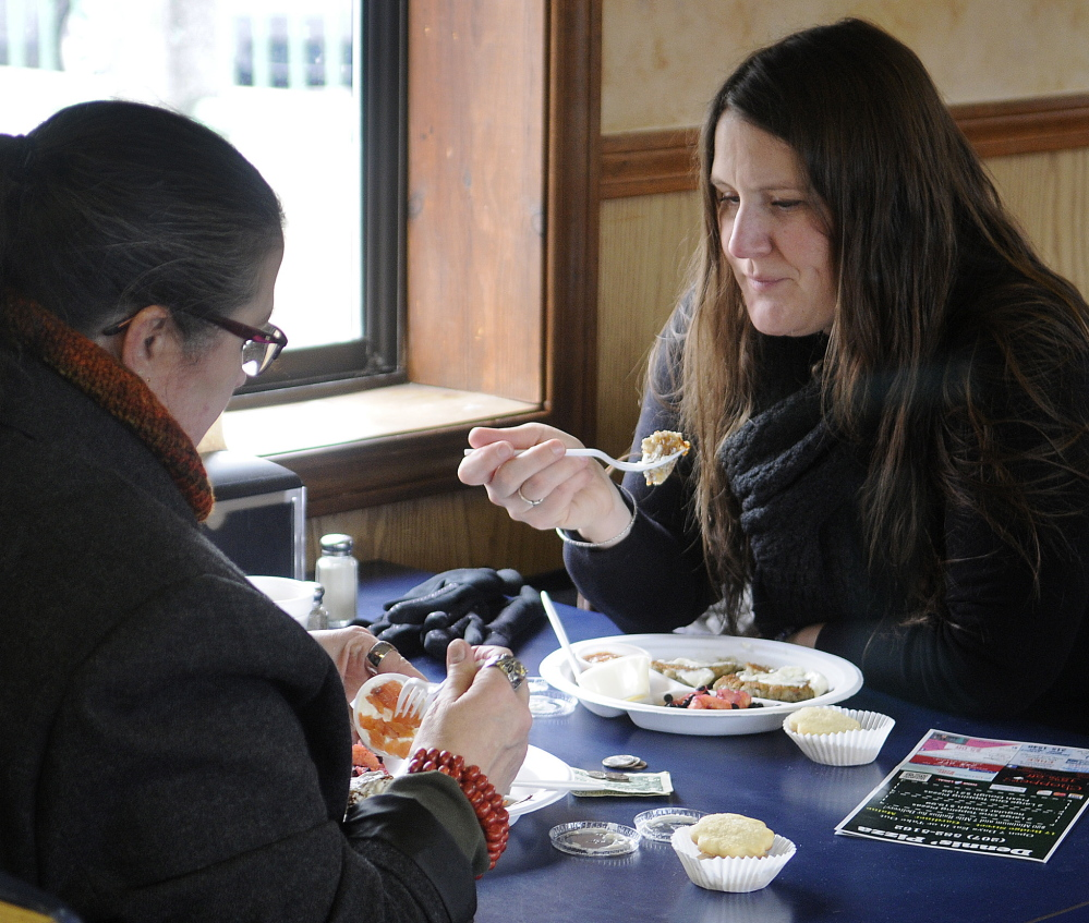 Dawn Thistle, right, and her mother, Marguerite Ridgway, eat latkes Sunday at Dennis' Pizza, which hosted Gardiner's annual latke party in observance of Hanukkah.