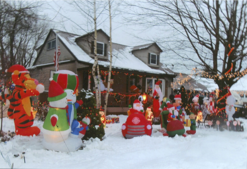 Contributed photo   Joan and Arnold Ricker Jr. of Augusta have decorated their house for Christmas with 14 blow up figures, including Tiger, Santa Clauses, a Mickey Mouse, Scooby Doo, Winnie the Pooh, penguins and more. They've also put lights on their porch, trees and bushes.