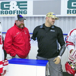 Spencer Buck, left, assistant coach Chris Buck, Travis Mills, who will do the honorary puck drop, and Tyler Curtis chat on Cony bench before a game against Gardiner on Saturday at the Bank of Maine Ice Vault in Hallowell.