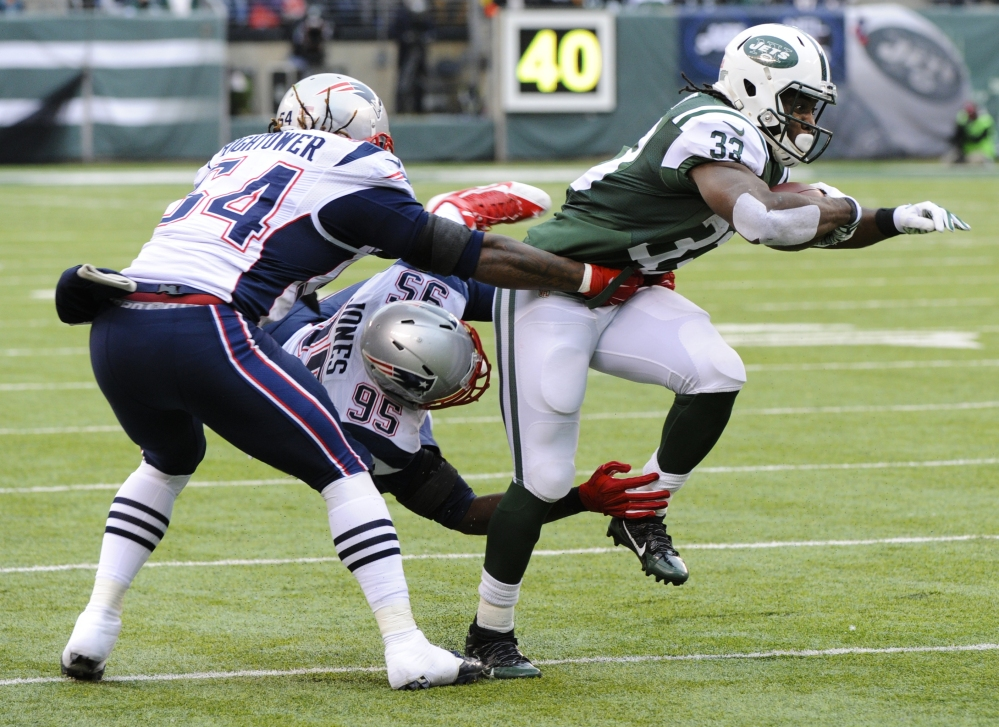New York Jets running back Chris Ivory (33) breaks a tackle by New England Patriots' Chandler Jones (95) and Dont'a Hightower (54) during the first half Sunday in East Rutherford, N.J. The Patriots won 17-16.
