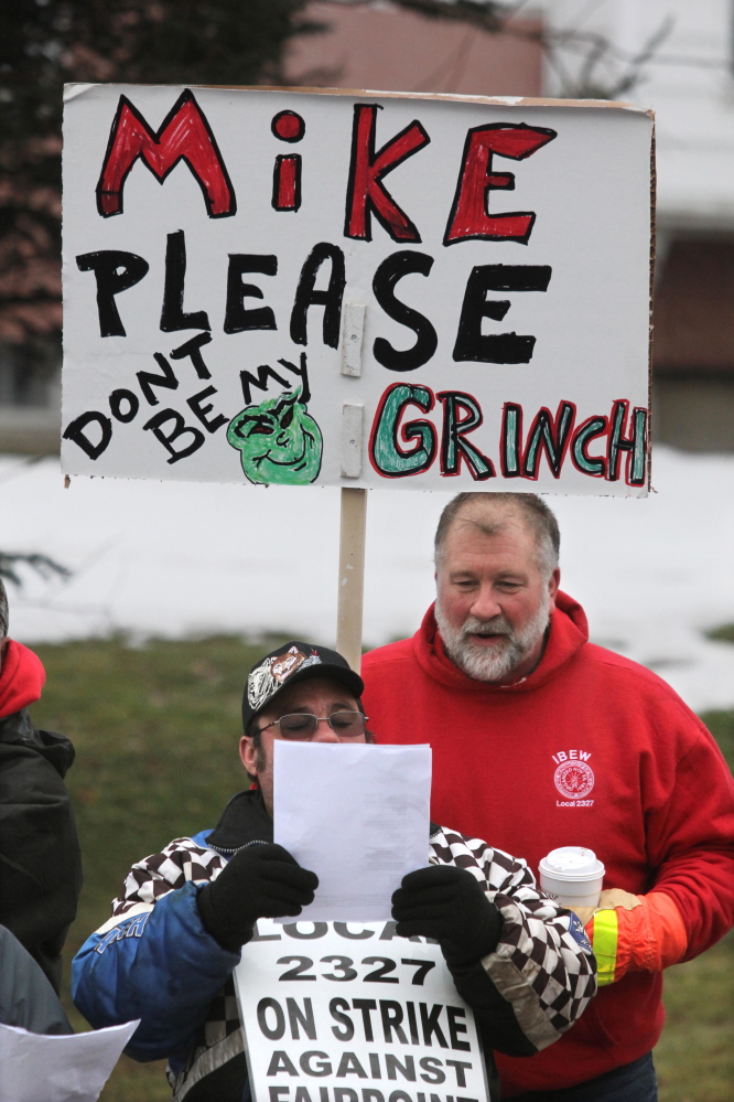Jim Feeney Jr. of Carmel looks over the shoulder of a fellow striking FairPoint worker while singing Christmas carols outside the Winslow home of Mike Reed, state president for FairPoint in Maine, on Tuesday.