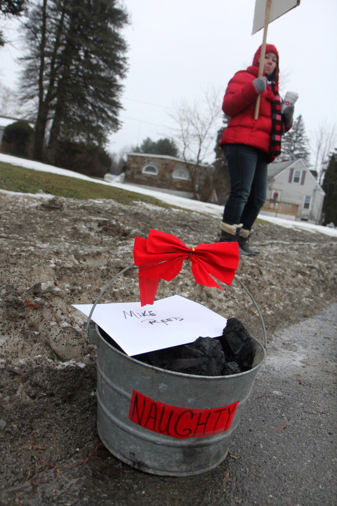 FairPoint workers put a bucket of coal on the sidewalk outside the Winslow home of Mike Reed, Maine president for Fairpoint, on Tuesday to symbolize their unhappiness with contract negotiations.