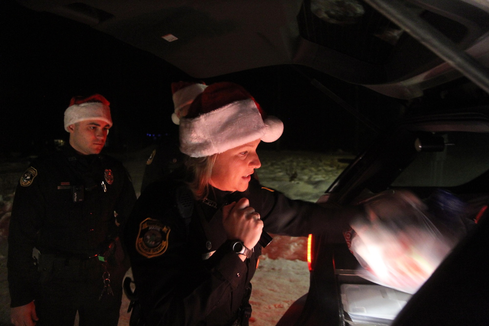 Fairfield police Officer Shanna Blodgett delivers Christmas presents on Tuesday night to local families on Martin Stream Road with fellow officers Jordan Brooks, left, and Patrick Mank.