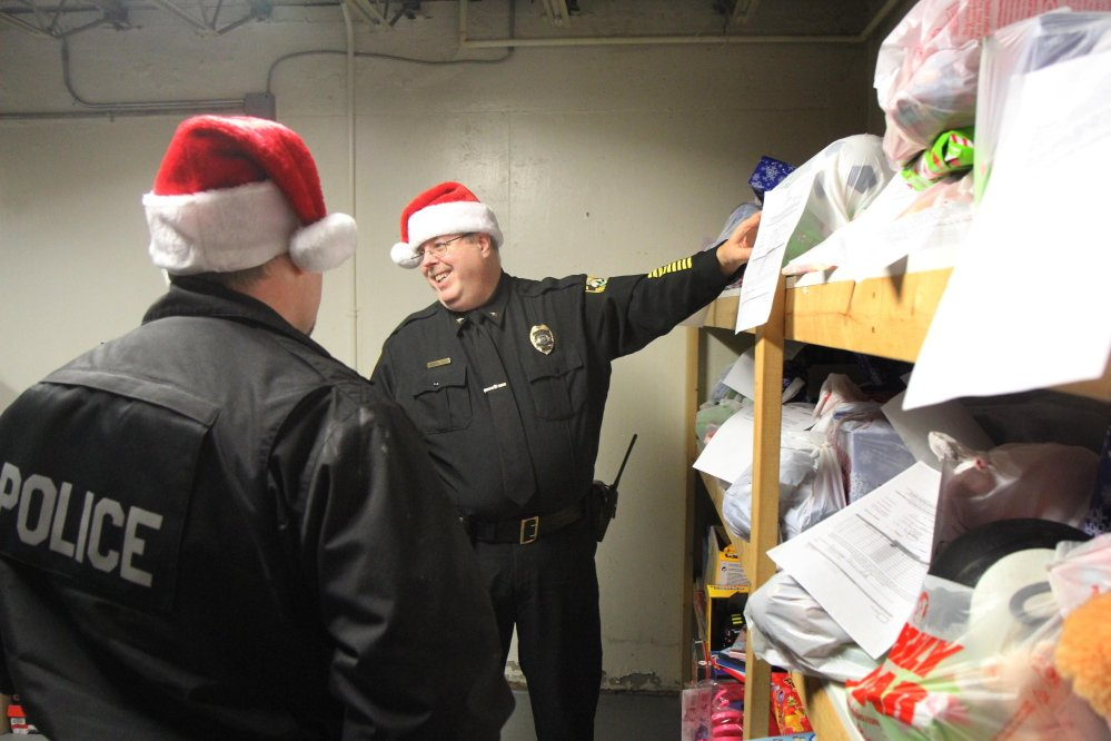 Fairfield Police Chief Thomas Gould pulls Christmas presents off the shelf Tuesday for his officers to deliver to local families.