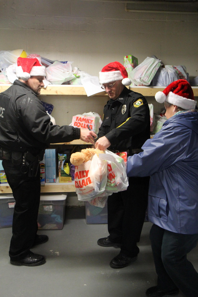Fairfield police Officers Matthew Wilcox, left, and William Beaulieu, center, along with volunteer Marlene Angers, organize Christmas presents to be delivered to local families on Tuesday night in Fairfield.