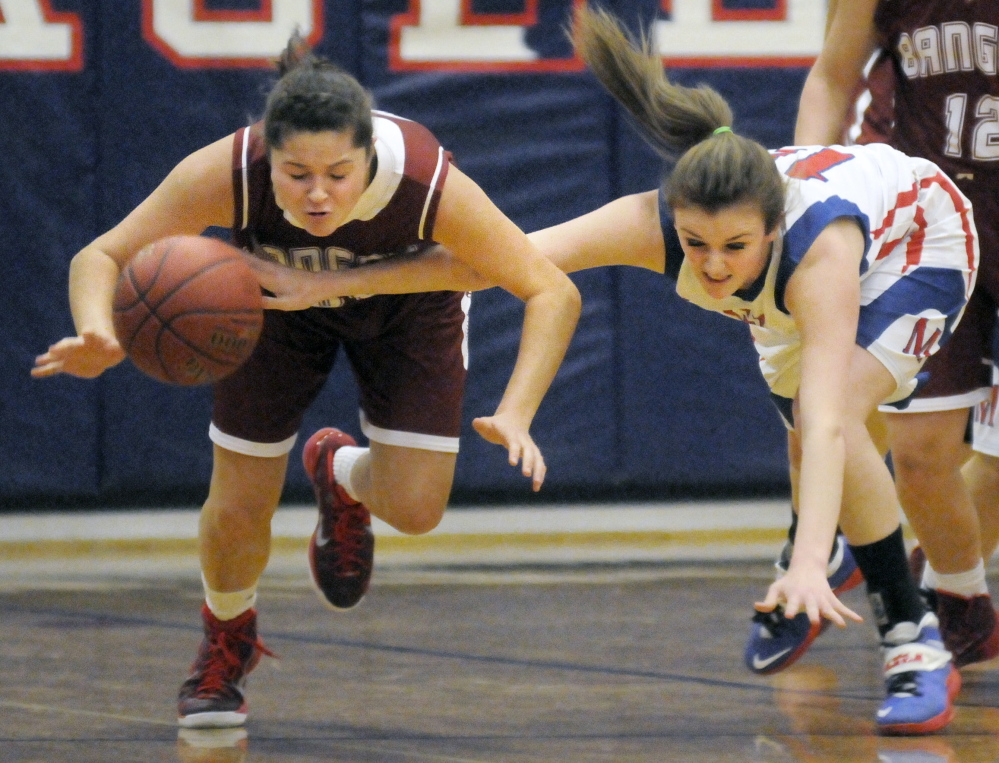 Messalonskee High School's Makayla Wilson, right, pushes the ball away from Bangor High School's Emily Gilmore during a game Tuesday in Oakland.