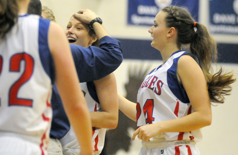 Messalonskee High School's Sophia Holmes, center, gets a pat on the head by coach Keith Derobsy during a timeout against Bangor High School on Tuesday in Oakland.